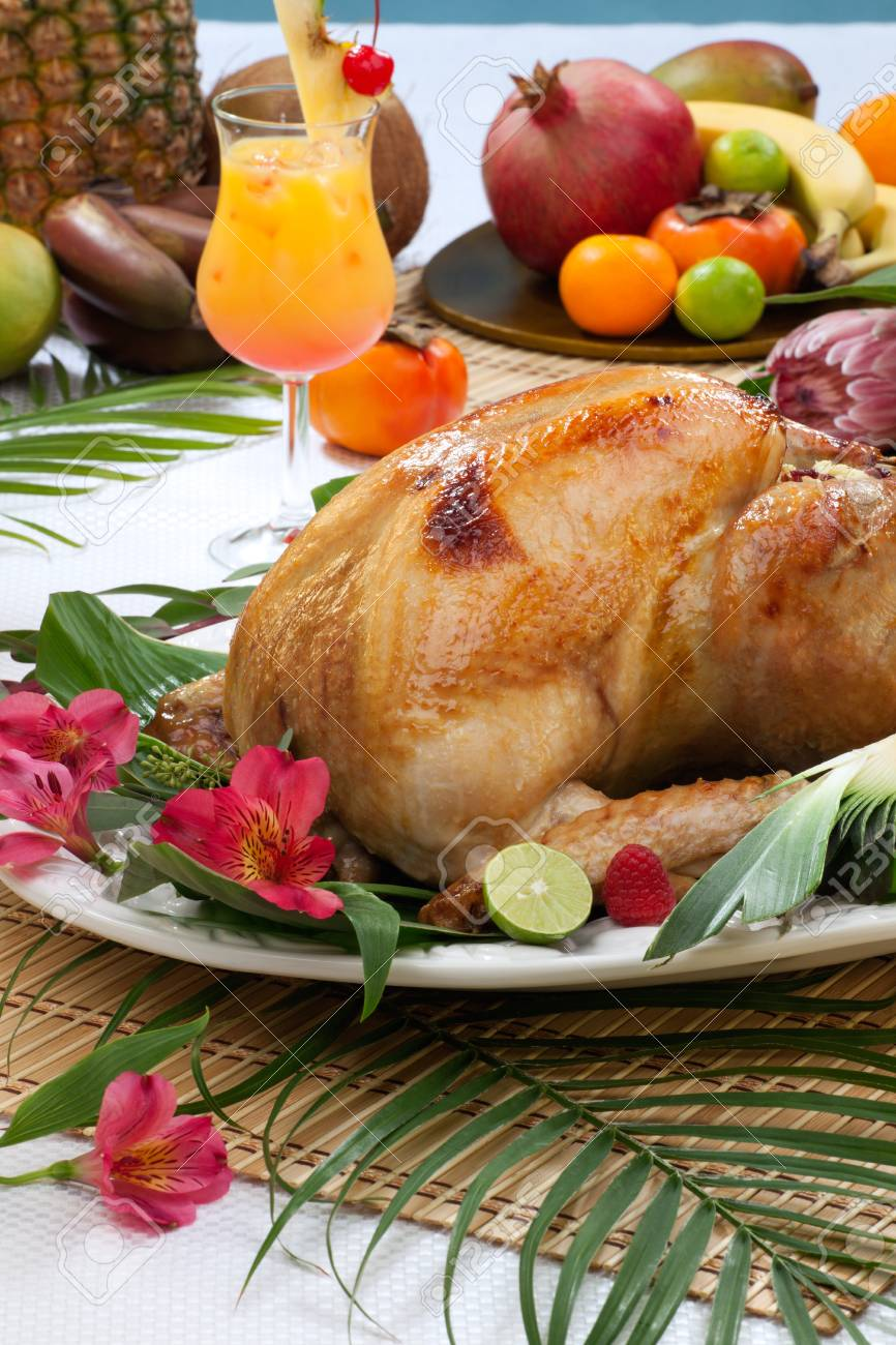 Garnished roasted turkey with tropical fruits, flowers, and refreshing cocktails for Thanksgiving. Stock Photo - 22120402
