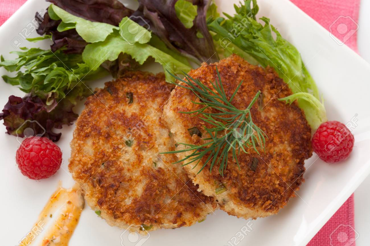 Two crab cakes appetizer garnished with spicy sauce, green salad, and raspbery - 22659382