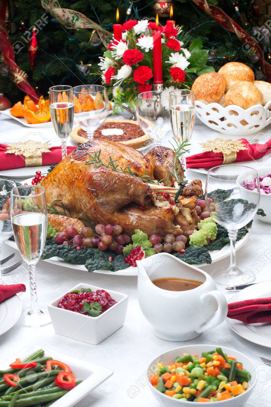 Holiday-decorated table, Christmas tree, champagne, and roasted turkey - 22659365