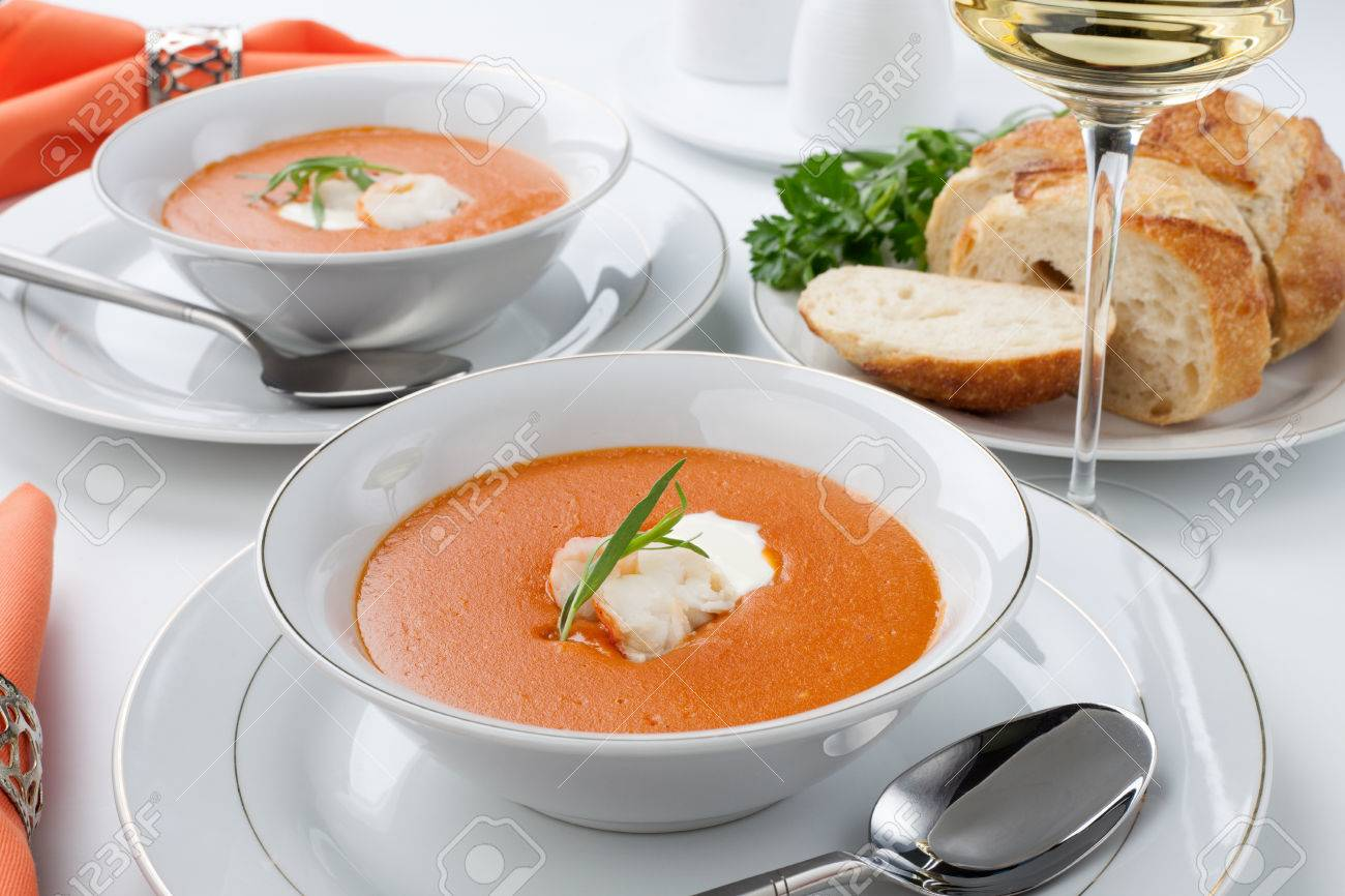 Two bowls of lobster bisque garnished with slice of lobster tail, cream, and fresh tarragon Fresh backed Italian bread and white wine - 26586455