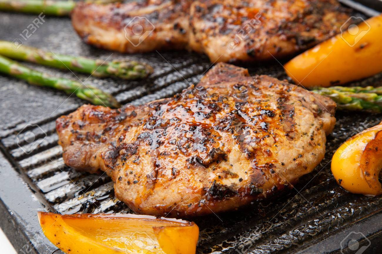 Juicy Pork Chops Are Grilled On Griddle With Asparagus And Bell Pepper  Backyard Grilling For Summer How To Cook