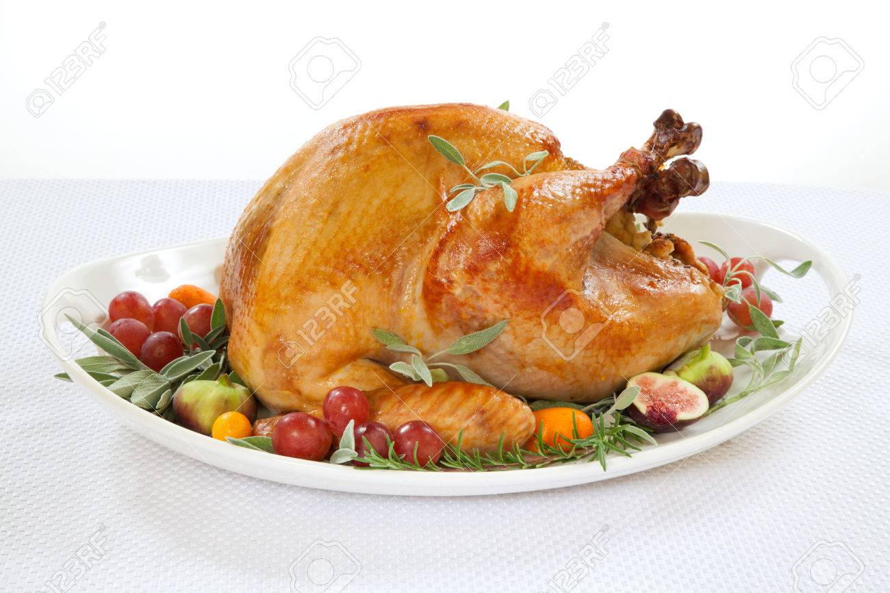 Roasted turkey on tray garnished with red grapes, figs, kumquat, and herbs over white background - 30467744