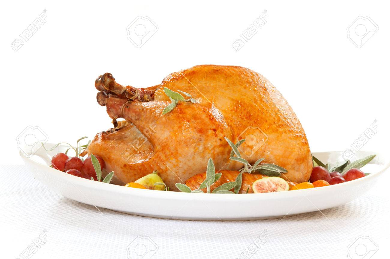 Roasted turkey on tray garnished with red grapes, figs, kumquat, and herbs over white - 30647610