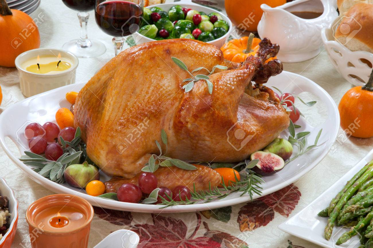 Roasted turkey on a server tray garnished with fresh figs, grape, kumquat, and herbs on fall harvest table. Red wine, side dishes, pie, and gravy. Decoraded with mini pumpkins, candels, and flowers. - 31463218
