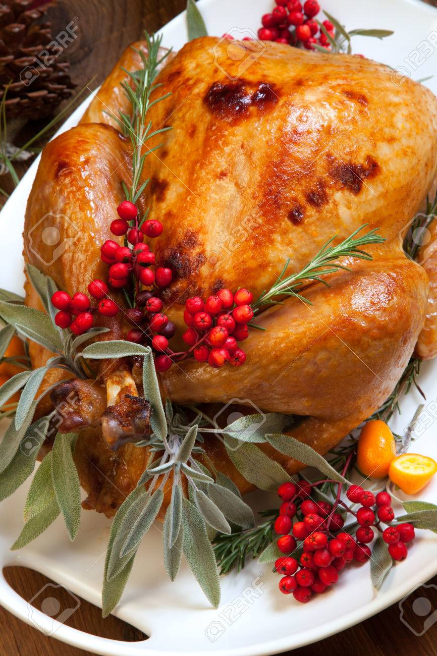 Roasted turkey garnished with sage, rosemary, and red berries in a tray prepared for Christmas dinner. Holiday table, candles and Christmas tree with ornaments. - 32774861
