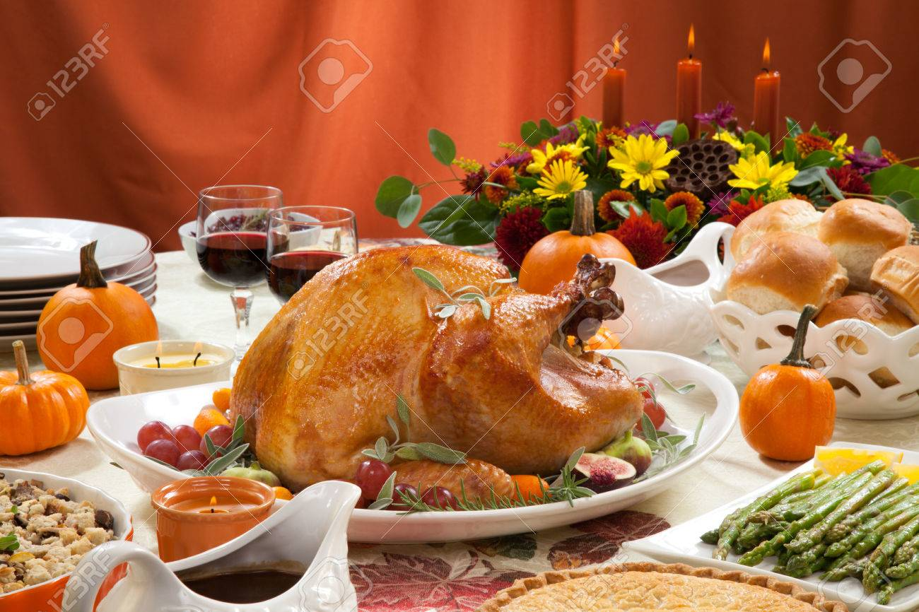 Roasted turkey on a server tray garnished with fresh figs, grape, kumquat, and herbs on fall harvest table. Red wine, side dishes, pie, and gravy. Decoraded with mini pumpkins, candels, and flowers. - 32816621