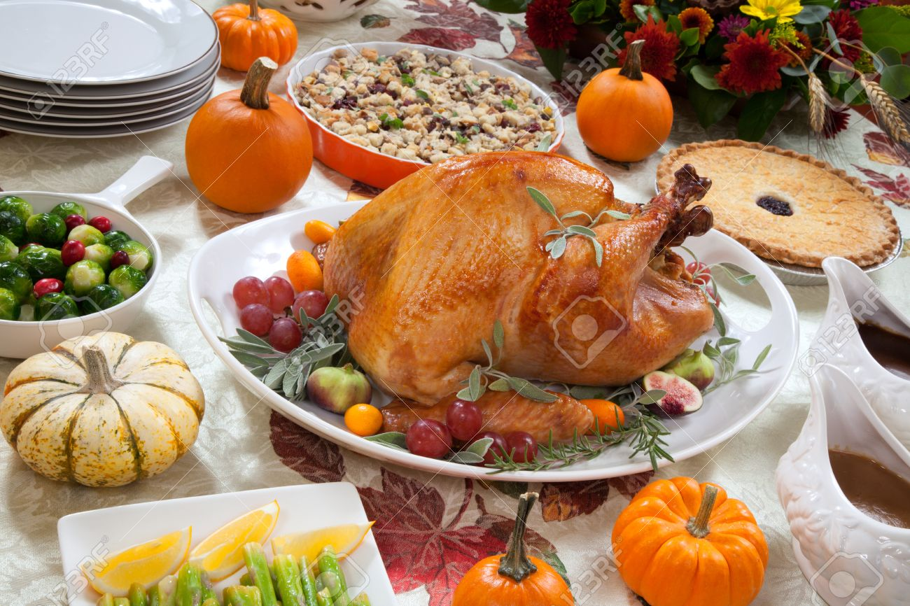 Roasted turkey on a server tray garnished with fresh figs, grape, kumquat, and herbs on fall harvest table. Red wine, side dishes, pie, and gravy. Decoraded with mini pumpkins, candels, and flowers. - 33345744