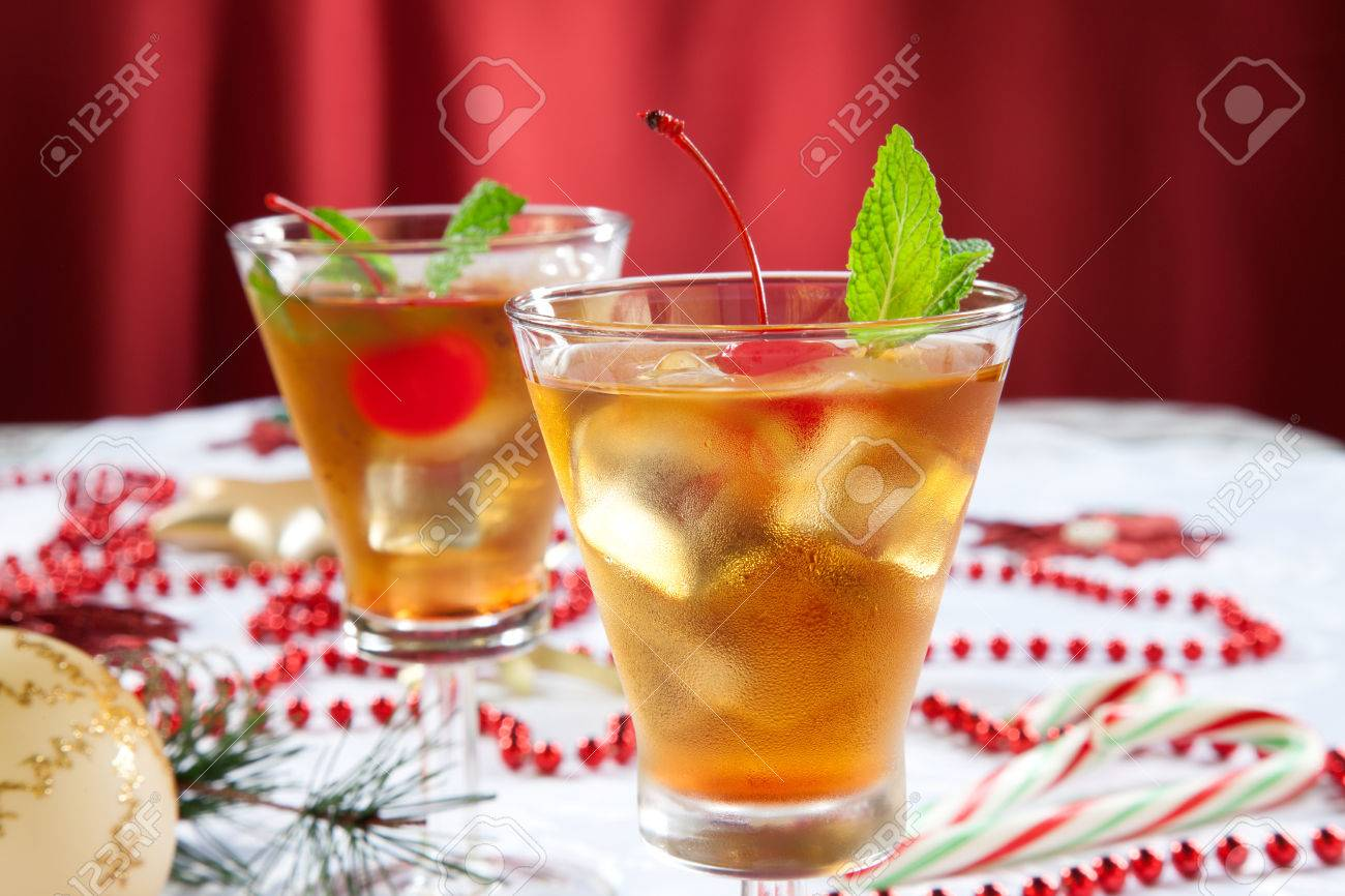 glasses of mint manhattan cocktails surrounded with christmas