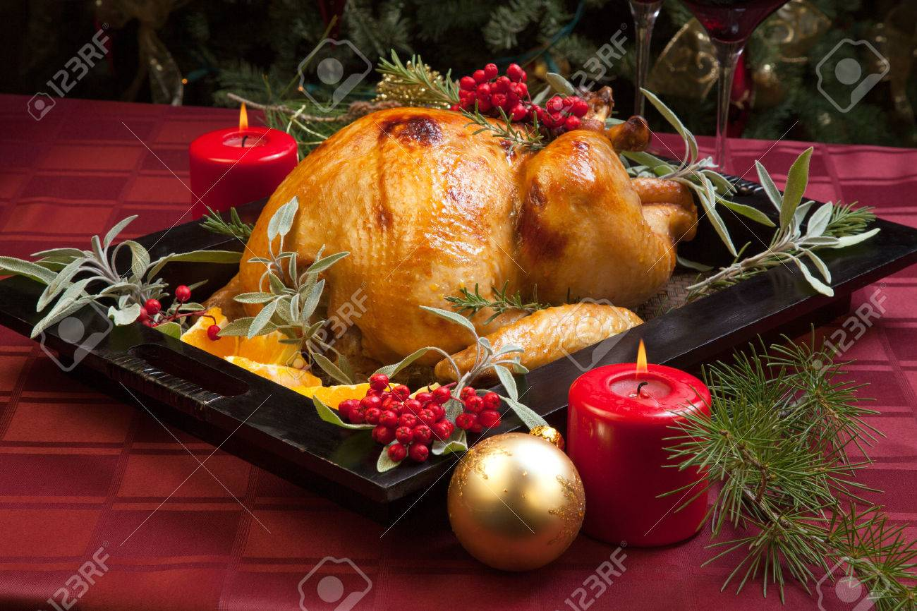 Roasted turkey garnished with sage, rosemary, and red berries in a wooden tray on Christmas decorated table. Candles and Christmas tree with ornaments. - 34609554