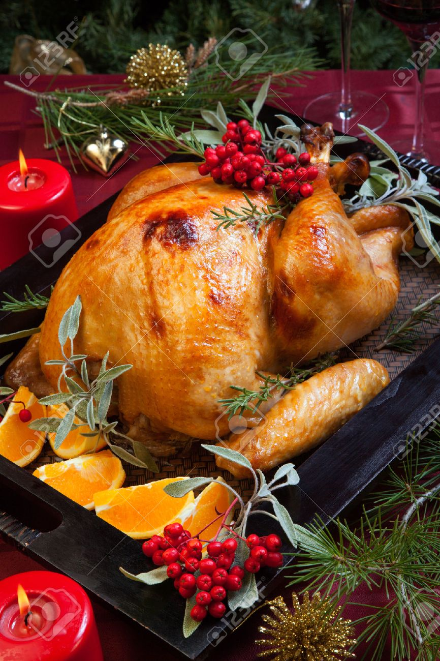 Roasted turkey garnished with sage, rosemary, and red berries in a wooden tray on Christmas decorated table. Candles and Christmas tree with ornaments. - 34780682