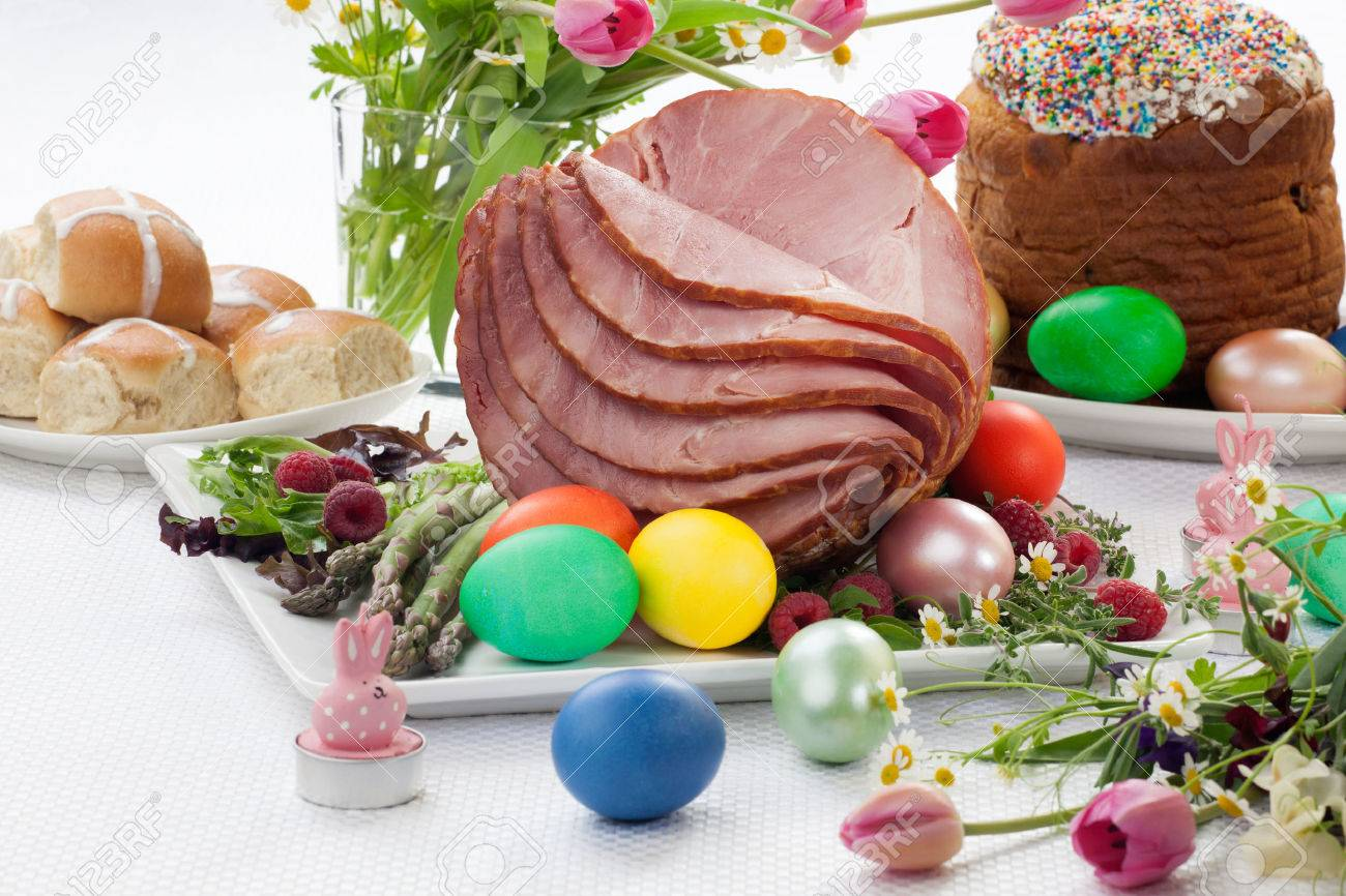 Whole baked honey sliced ham with fresh raspberry, asparagus, dyed Ester eggs, Easter cake, and cross buns. Spring flowers. - 35101024