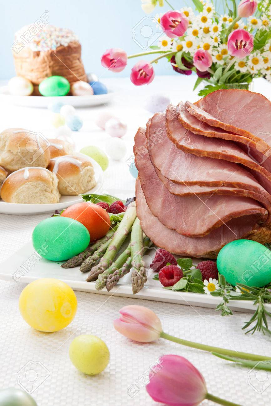 Whole baked honey sliced ham with fresh raspberry, asparagus, dyed Ester eggs, Easter cake, and cross buns. Spring flowers. - 35347317