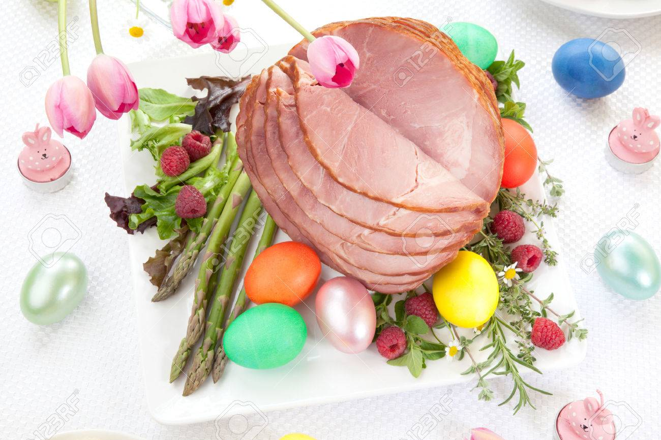 Whole baked honey sliced ham with fresh raspberry, asparagus, dyed Ester eggs, Easter cake, and cross buns. Spring flowers. - 37160817