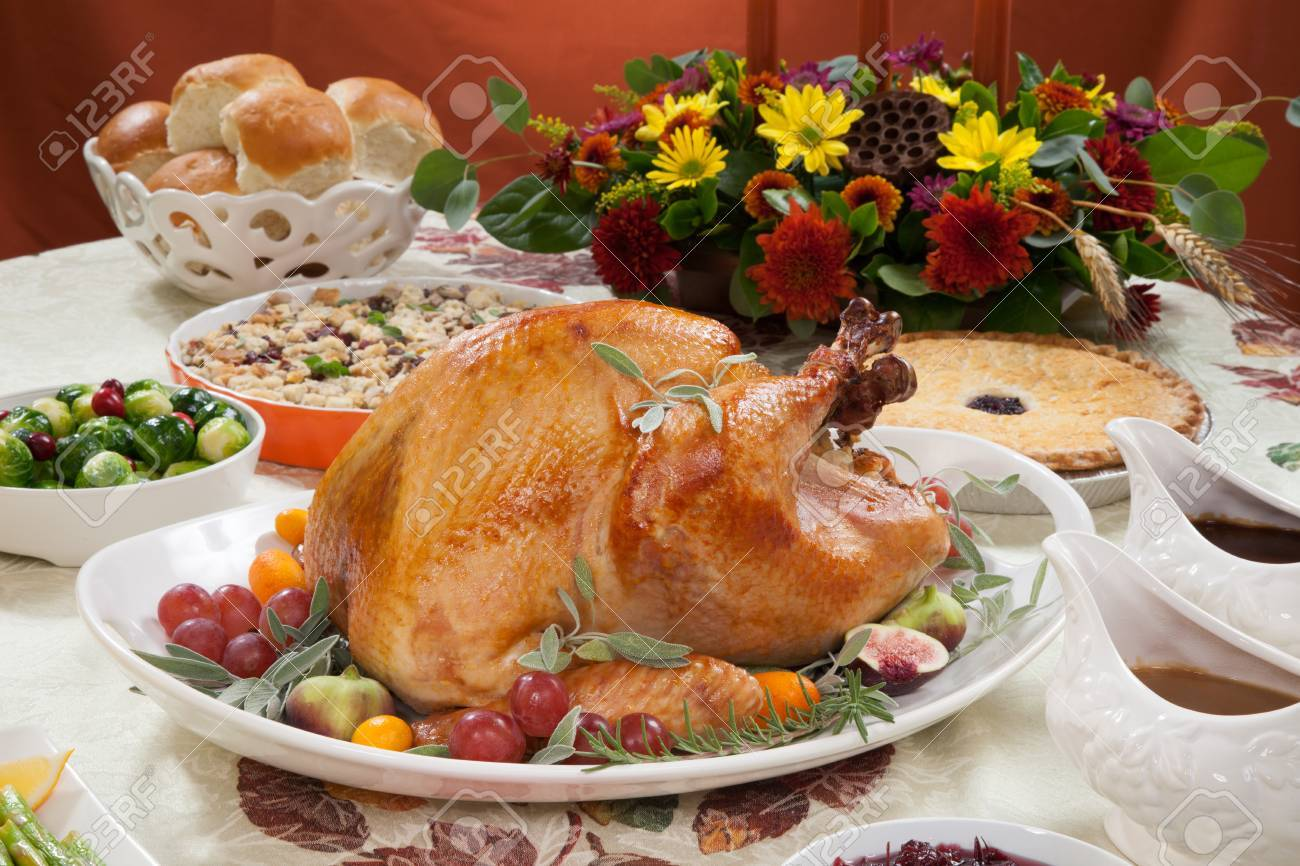Roasted turkey on a server tray garnished with fresh figs grape kumquat and herbs on fall harvest table. Red wine side dishes pie and gravy. Decoraded with mini pumpkins candels and flowers. - 41926300