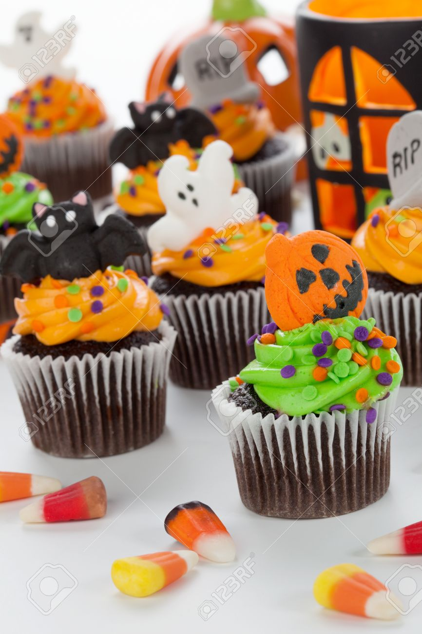 Halloween cupcake with jack,o,lantern and bat decorations surrounded by Halloween cupcakes