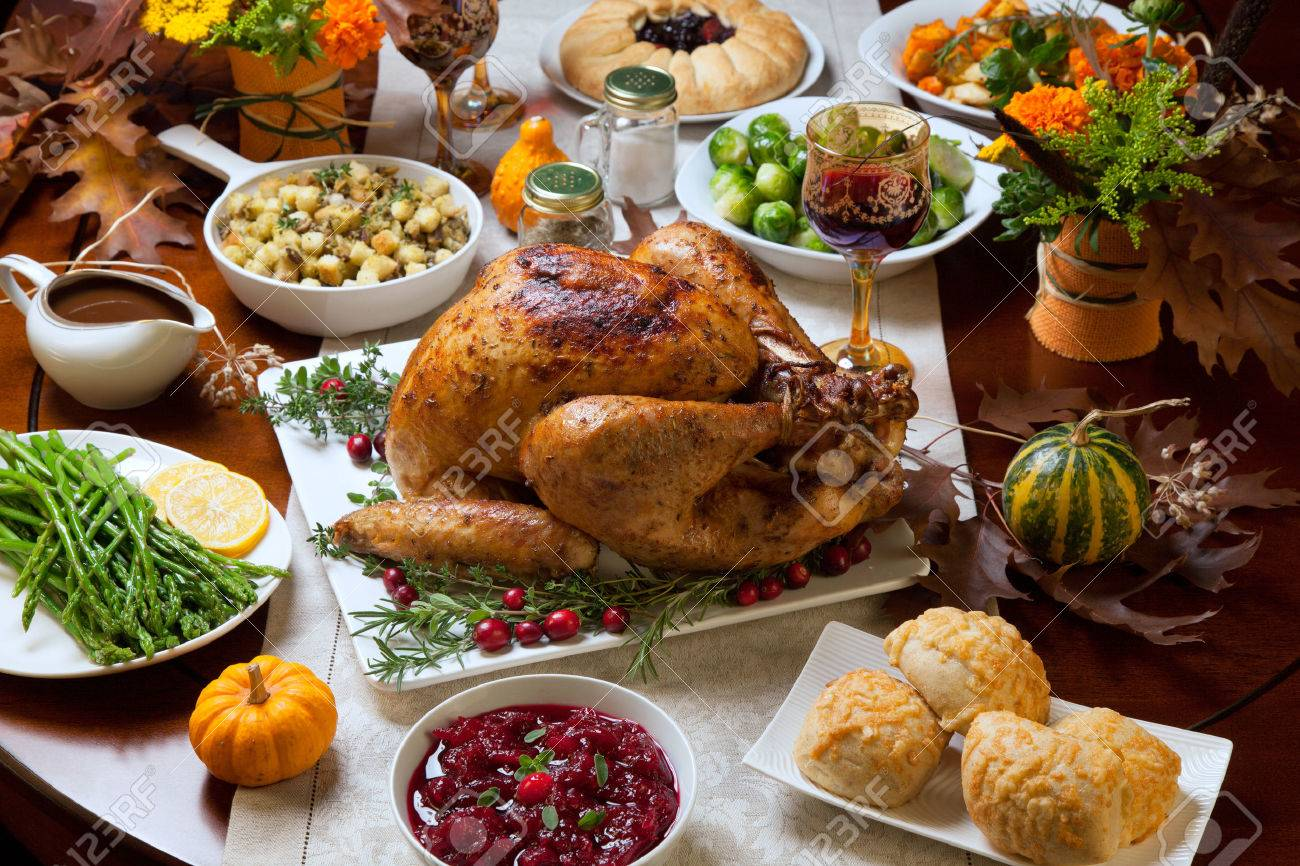 Roasted turkey garnished with cranberries on a rustic style table decoraded with pumpkins, gourds, asparagus, brussel sprouts, baked vegetables, pie, flowers, and candles. - 44237203
