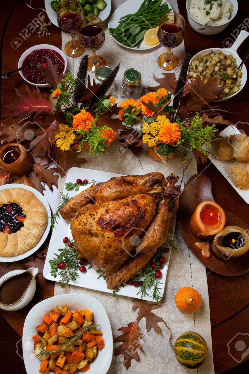 Roasted turkey garnished with cranberries on a rustic style table decoraded with pumpkins, gourds, asparagus, brussel sprouts, baked vegetables, pie, flowers, and candles. - 44237212