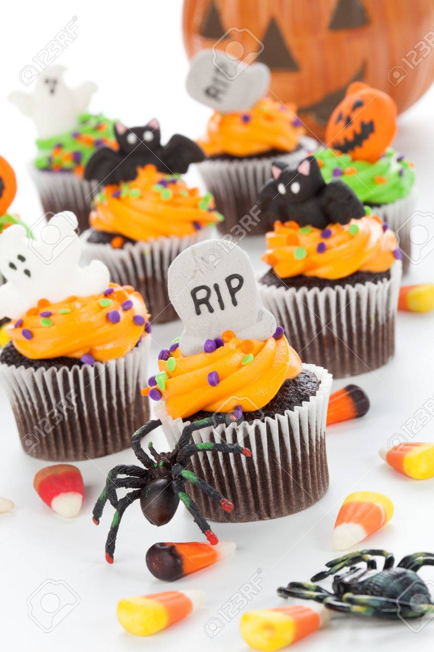 Halloween cupcake with RIP, ghost, and bat decorations surrounded by Halloween cupcakes, corn