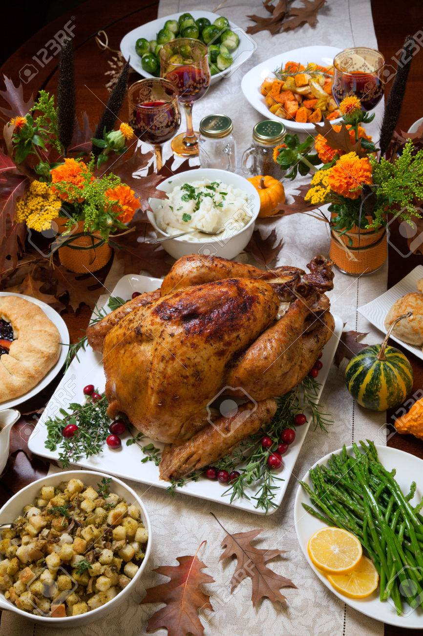 Roasted turkey garnished with cranberries on a rustic style table decoraded with pumpkins, gourds, asparagus, brussel sprouts, baked vegetables, pie, flowers, and candles. - 46421061