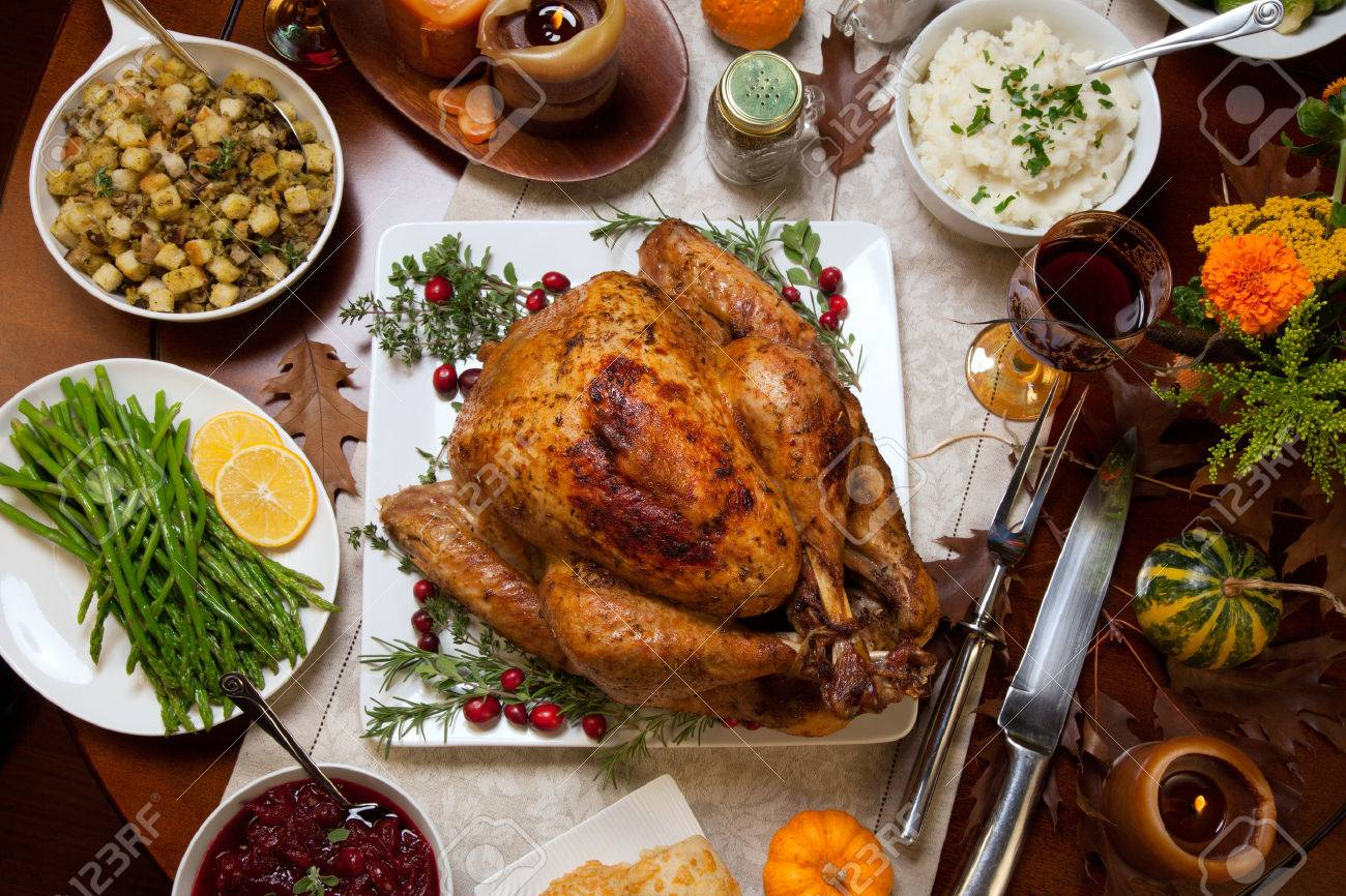Roasted turkey garnished with cranberries on a rustic style table decoraded with pumpkins, gourds, asparagus, brussel sprouts, baked vegetables, pie, flowers, and candles. - 46860336