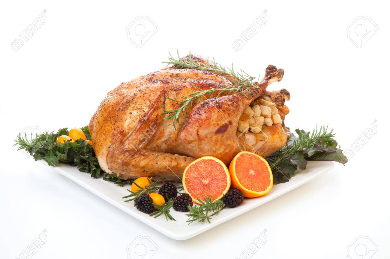 Roasted stuffed turkey garnished with fresh fruits and herbs for holiday dinner. - 46728079