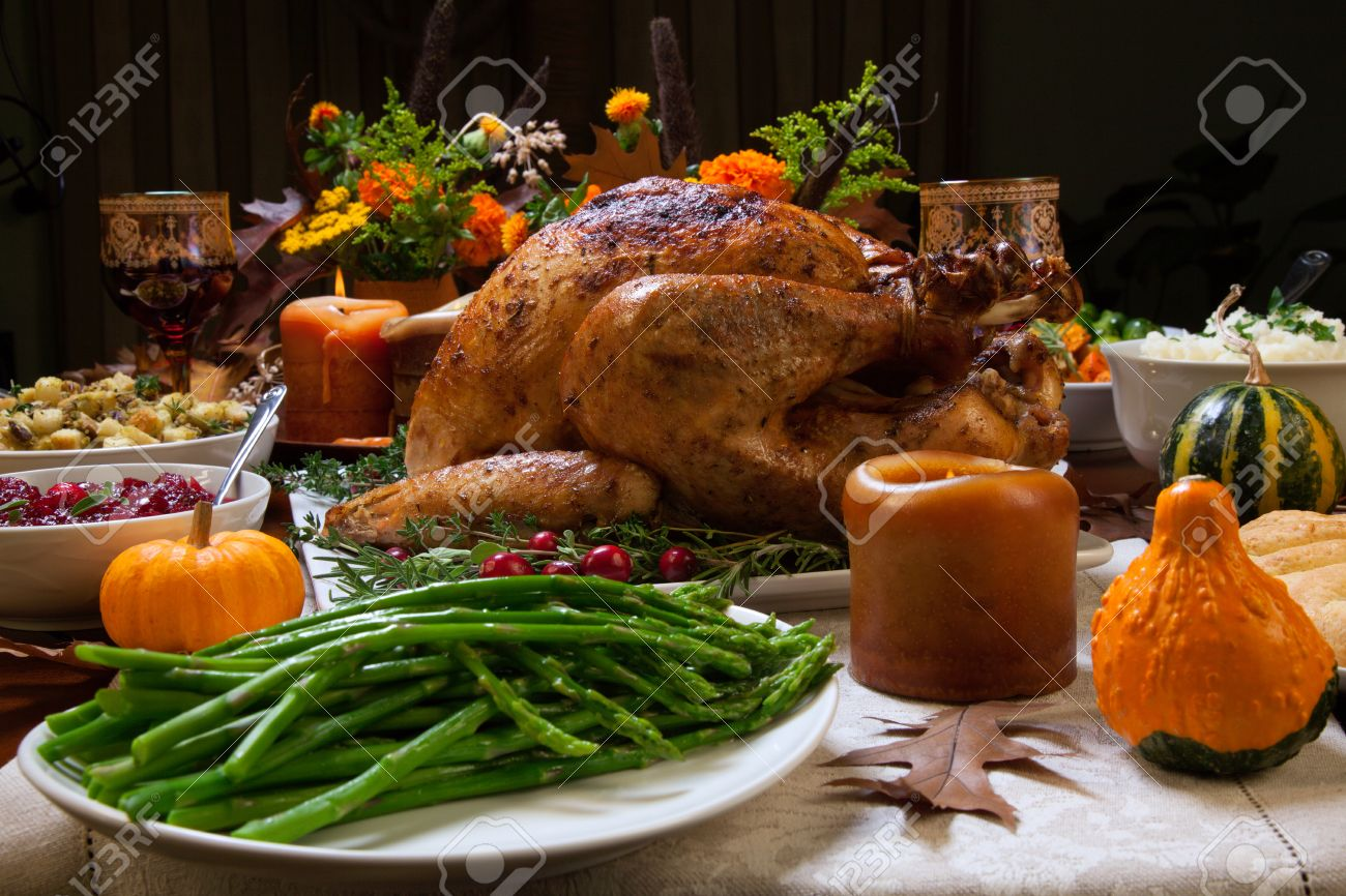 Roasted turkey garnished with cranberries on a rustic style table decoraded with pumpkins, gourds, asparagus, brussel sprouts, baked vegetables, pie, flowers, and candles. - 47018834
