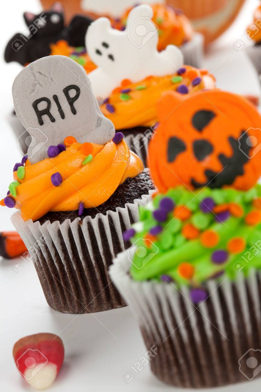 halloween cupcake with rip ghost and bat decorations surrounded by halloween cupcakes corn
