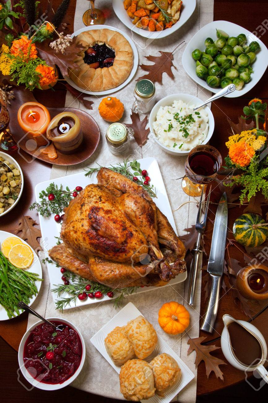 Roasted turkey garnished with cranberries on a rustic style table decoraded with pumpkins, gourds, asparagus, brussel sprouts, baked vegetables, pie, flowers, and candles. - 47018840