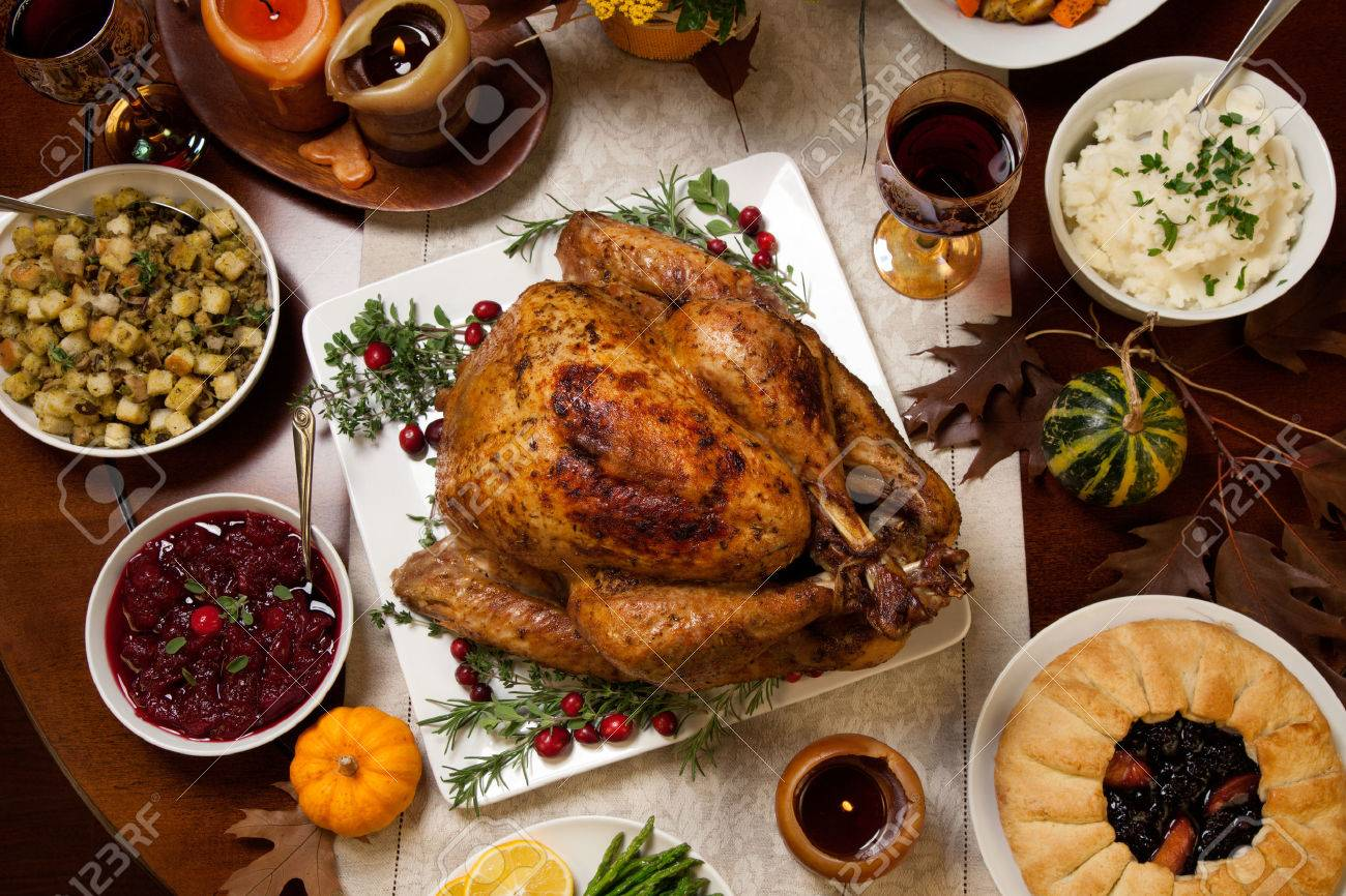 Roasted turkey garnished with cranberries on a rustic style table decoraded with pumpkins, gourds, asparagus, brussel sprouts, baked vegetables, pie, flowers, and candles. - 47018883