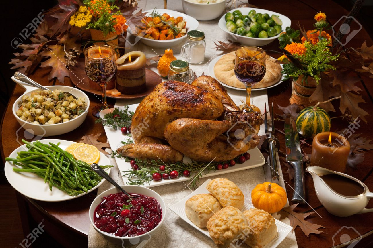 Roasted turkey garnished with cranberries on a rustic style table decoraded with pumpkins, gourds, asparagus, brussel sprouts, baked vegetables, pie, flowers, and candles. - 48015244