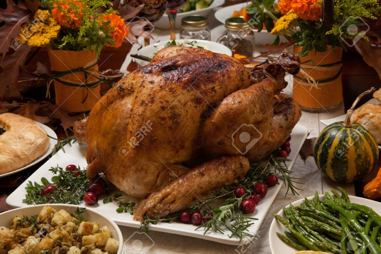 Roasted turkey garnished with cranberries on a rustic style table decoraded with pumpkins, gourds, asparagus, brussel sprouts, baked vegetables, pie, flowers, and candles. - 48590901