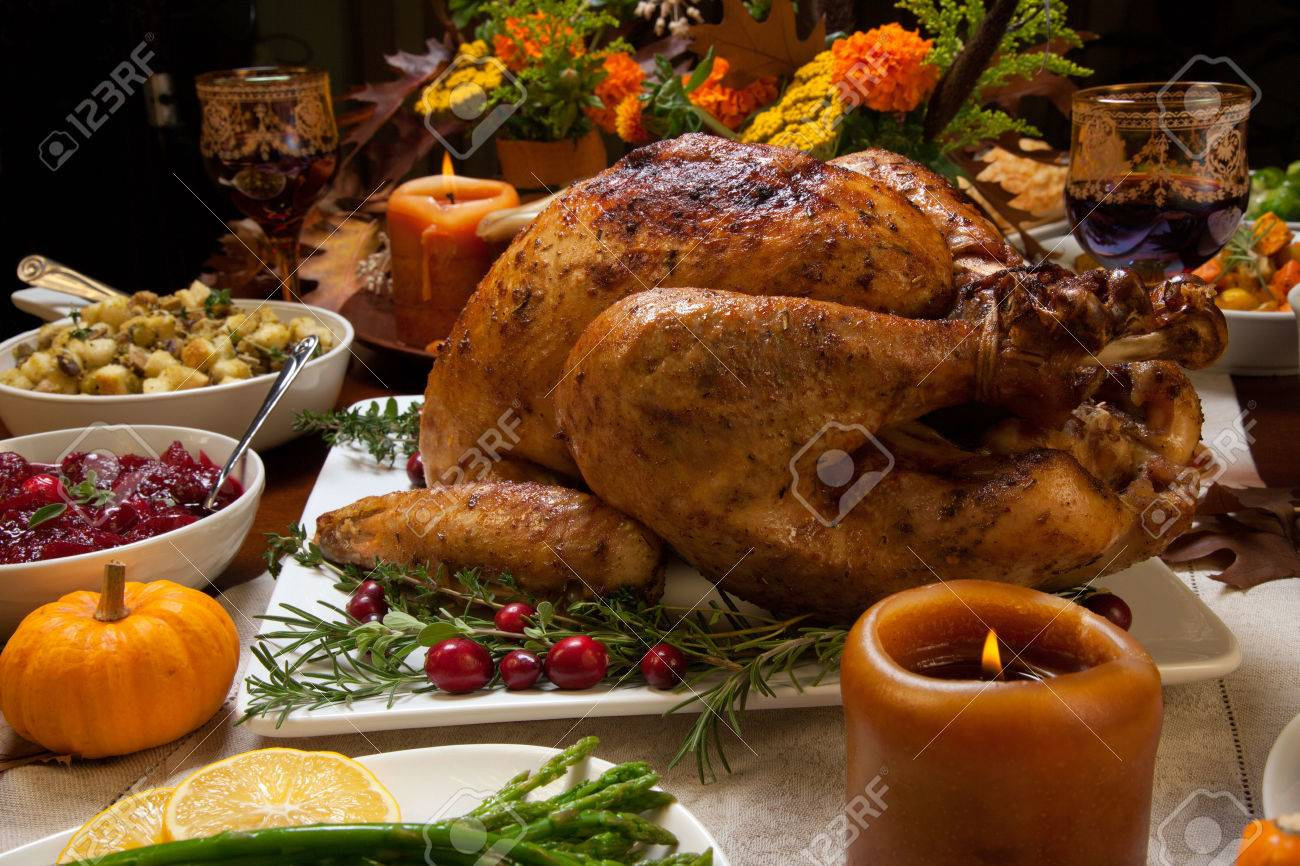 Roasted turkey garnished with cranberries on a rustic style table decoraded with pumpkins, gourds, asparagus, brussel sprouts, baked vegetables, pie, flowers, and candles. - 48887554