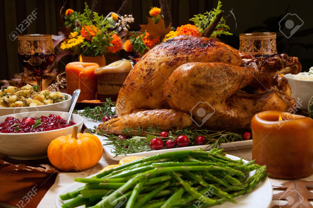 Roasted turkey garnished with cranberries on a rustic style table decoraded with pumpkins, gourds, asparagus, brussel sprouts, baked vegetables, pie, flowers, and candles. - 49021202