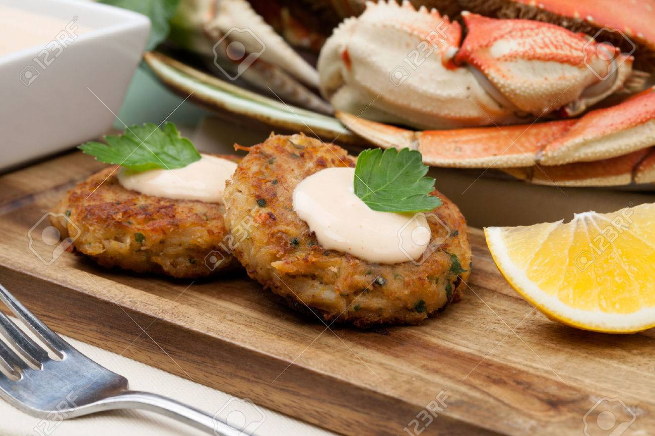 Three crab cakes appetizer with spicy sauce and fresh parsley. Dungeness crab in the background. - 58390544