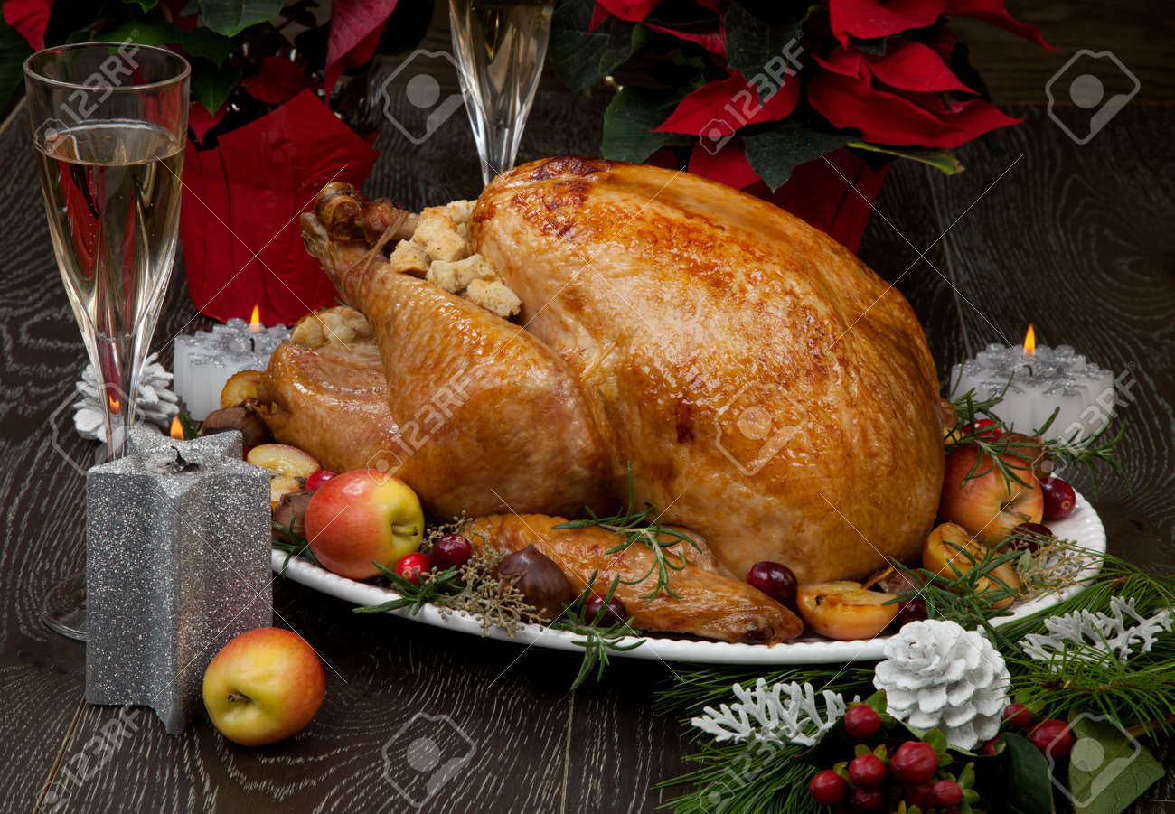 Garnished roasted Christmas turkey with grab apples, sweet chestnut, cranberry, Christmas ornaments, candles, and pine cones. - 131298436