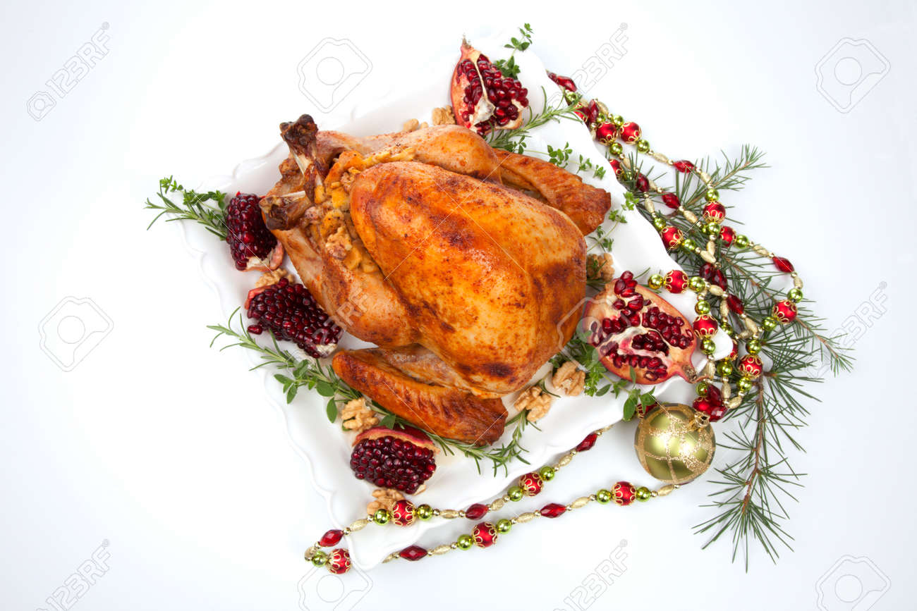 Pomegranate glazed roasted turkey on a tray garnished with fresh pomegranates, herbs, and walnuts over white background. Christmas ornaments and fir twigs. - 159848804