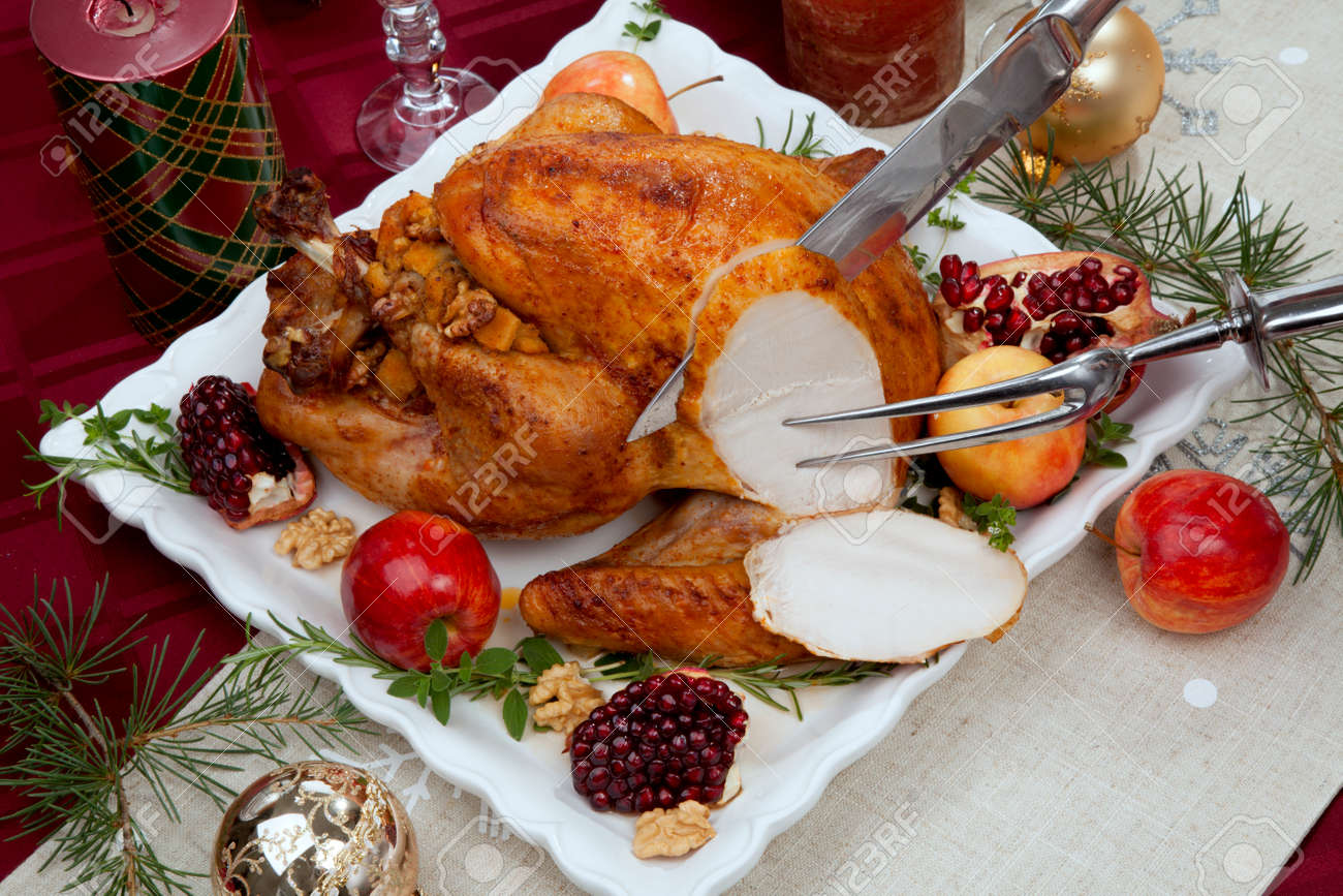 Carving pomegranate glazed roasted turkey on a tray garnished with fresh pomegranates, apples, herbs, and walnuts on Christmas-decorated table with candles, ornaments, fir twigs and flutes of champagne. - 160496017
