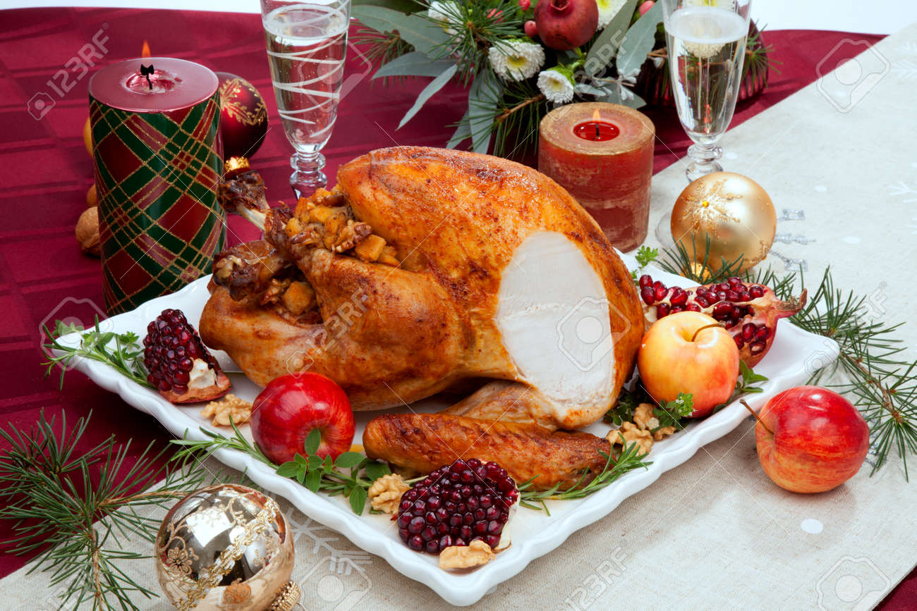 Carving pomegranate glazed roasted turkey on a tray garnished with fresh pomegranates, apples, herbs, and walnuts on Christmas-decorated table with candles, ornaments, fir twigs and flutes of champagne. - 160496062