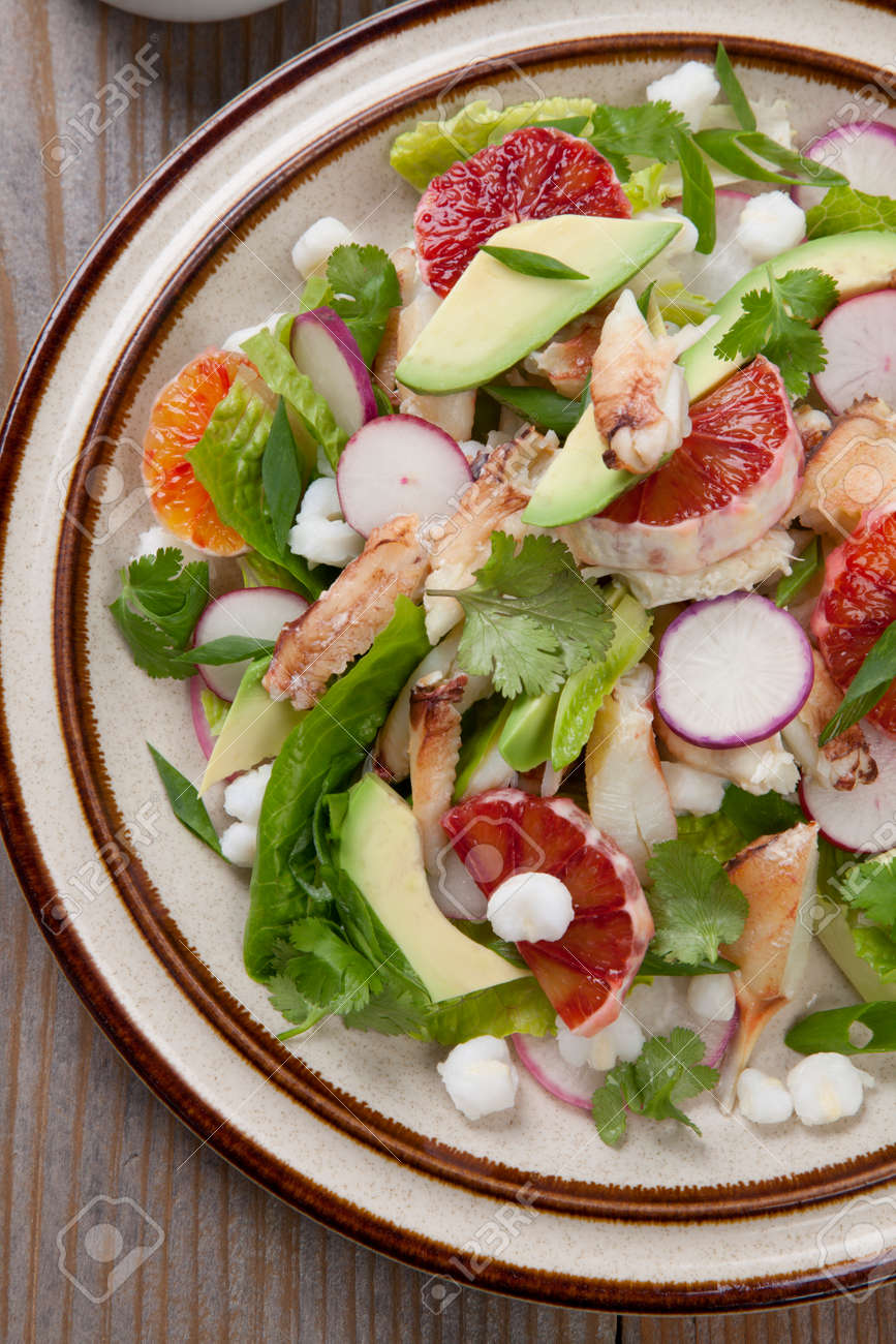 Fusion of Mexican cuisine and a traditional seafood crab salad. Closeup of Blood Orange Crab Posole Salad with fresh cooked Dungeness crab meat, avocado, radish, Romaine lettuce, and white hominy. - 160495890