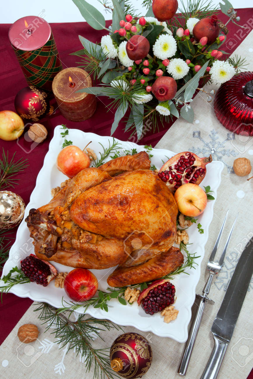 Pomegranate glazed roasted turkey on a tray garnished with fresh pomegranates, apples, herbs, and walnuts on Christmas-decorated table with candles, ornaments, fir twigs and flutes of champagne. - 160495688