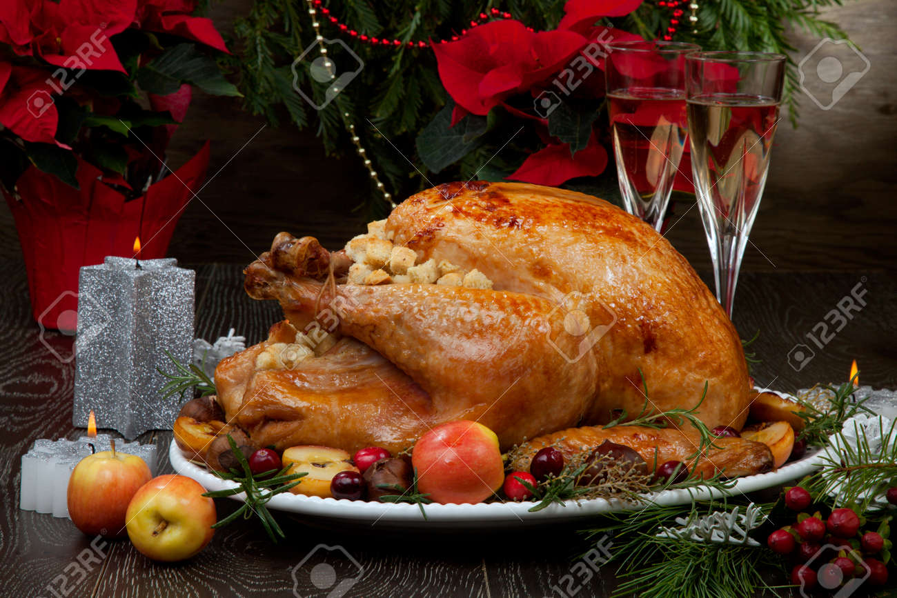 Garnished roasted Christmas turkey with grab apples, sweet chestnut, cranberry, Christmas ornaments, candles, and pine cones. - 160496205