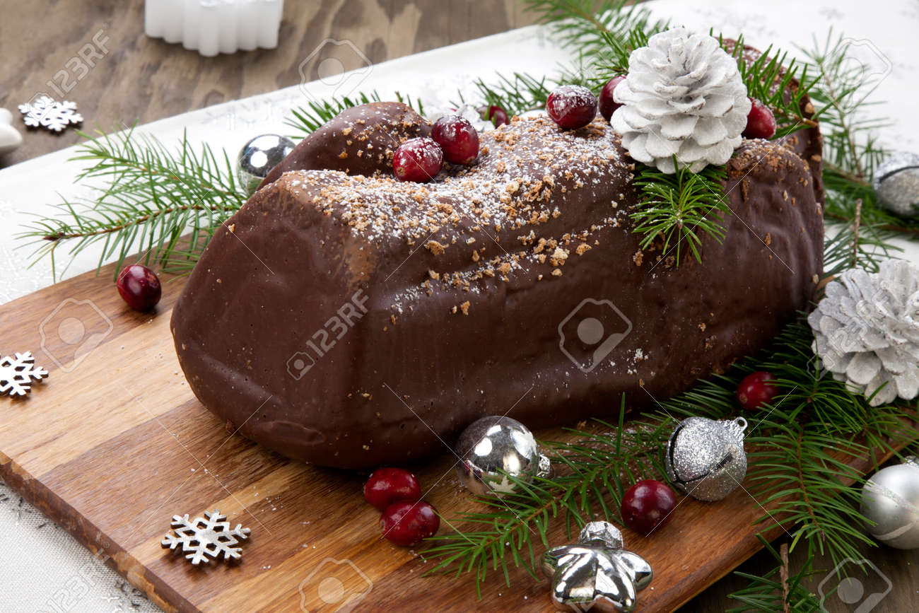 Traditional Christmas chocolate yule log cake with cranberry, Christmas ornamets, and decorations. - 160495923