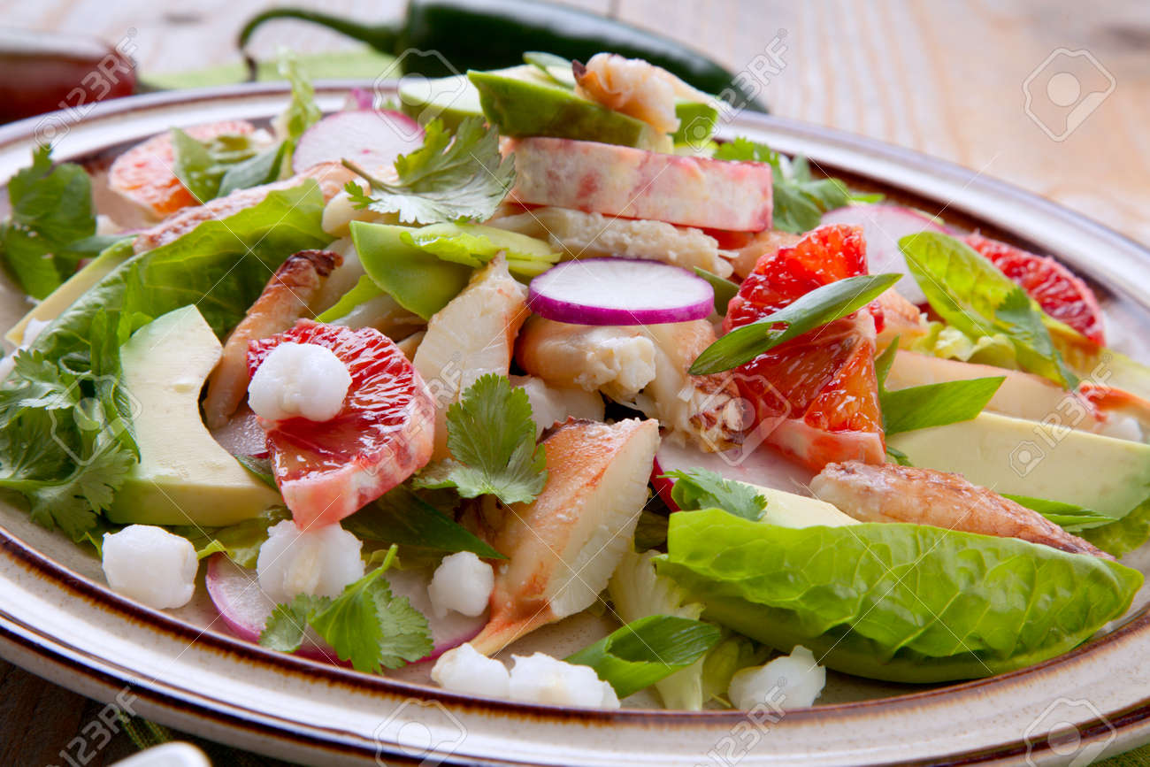 Fusion of Mexican cuisine and a traditional seafood crab salad. Closeup of Blood Orange Crab Posole Salad with fresh cooked Dungeness crab meat, avocado, radish, Romaine lettuce, and white hominy. - 162557484