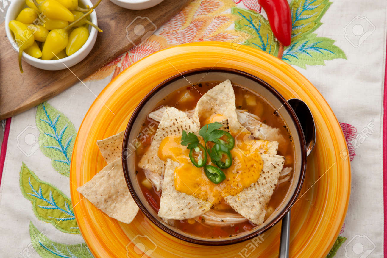 Closeup of a bowl of hot delicious spicy chicken nacho soup, garnished with melted cheese, jalapeno pepper, and fresh cilantro. Salsa, guacamole, and marinated hot pepper. - 162557490