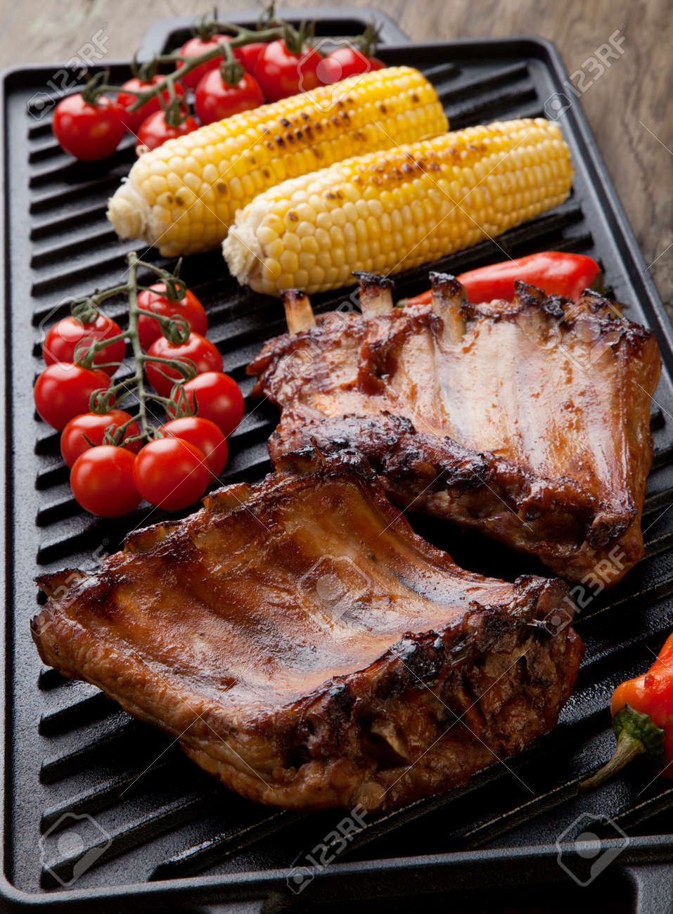Grilled pork ribs on griddle with chili pepper, cherry tomatoes, and grilled corn - 162557497