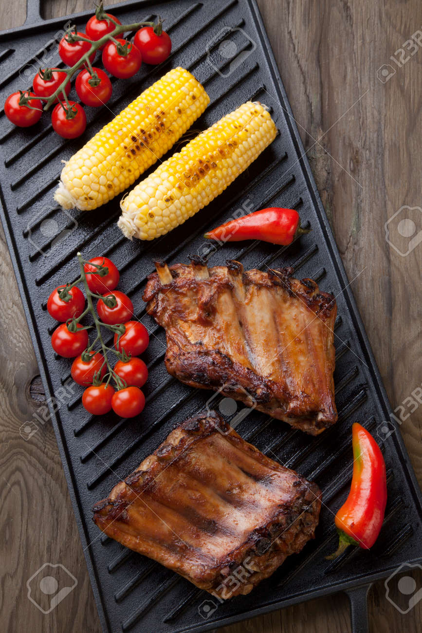Grilled pork ribs on griddle with chili pepper, cherry tomatoes, and grilled corn - 162557501