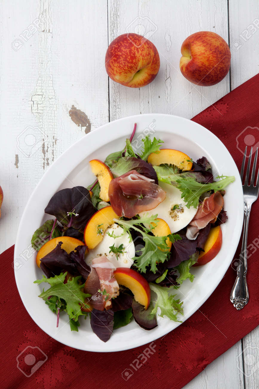 Closeup of Prosciutto peach salad with rresh Mozzarella plate mixed with spring greens. Freash peaches. - 164763899