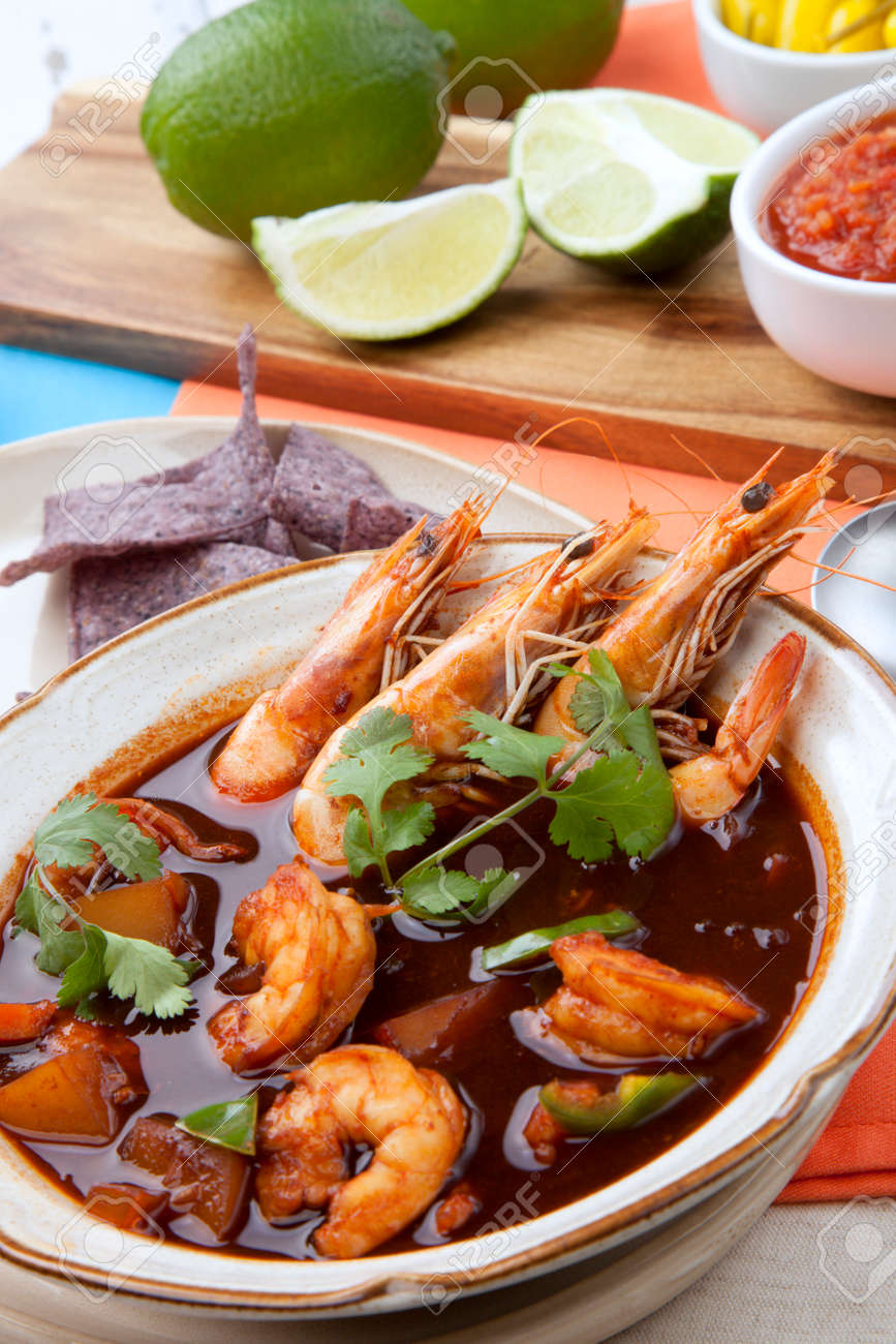 Closeup of a bowl of hot delicious spicy Mexican shrimp soup, garnished with whole shrimps and fresh cilantro. Limes, blue corn chips, salsa, guacamole, and marinated hot pepper. - 165786051