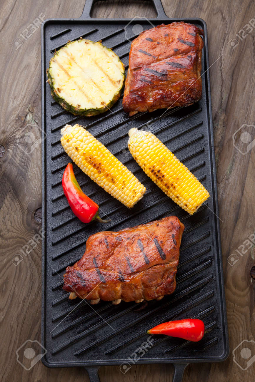 Grilled pork ribs on griddle with chili pepper, cherry tomatoes, and grilled corn - 165786052