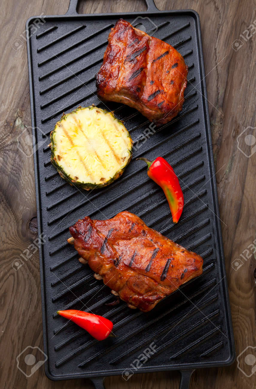 Grilled pork ribs on griddle with chili pepper and grilled pineapple. - 166715504